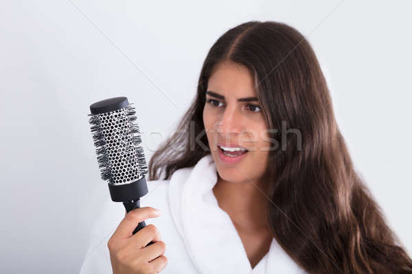 Woman In Bathrobe Holding Comb Looking At Hair Loss Stock photo © AndreyPopov