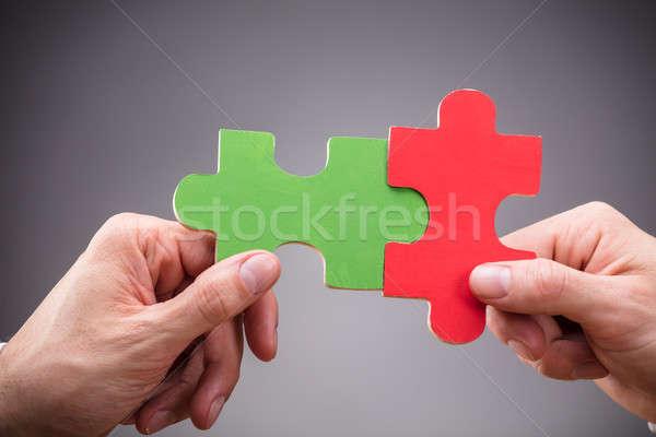 Két személy tart kirakós játék szürke közelkép piros Stock fotó © AndreyPopov