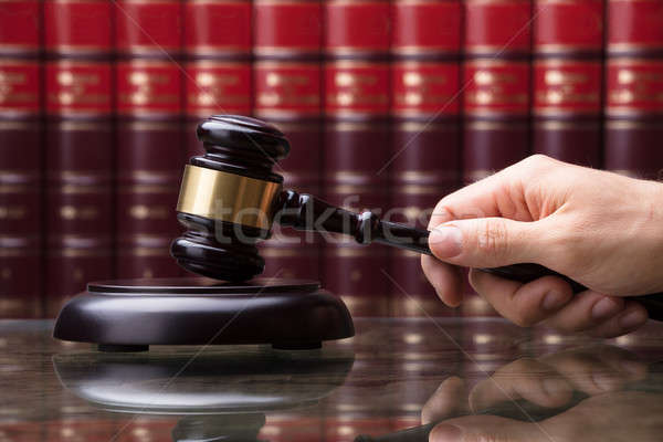 Person Striking Gavel On Sounding Block Stock photo © AndreyPopov