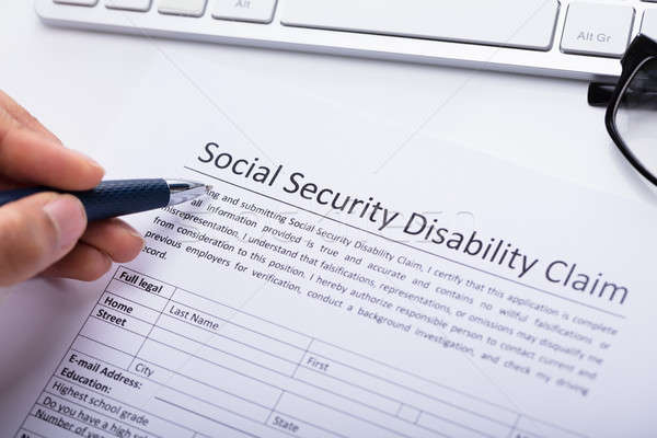 Person Filling Social Security Disability Claim Form Stock photo © AndreyPopov