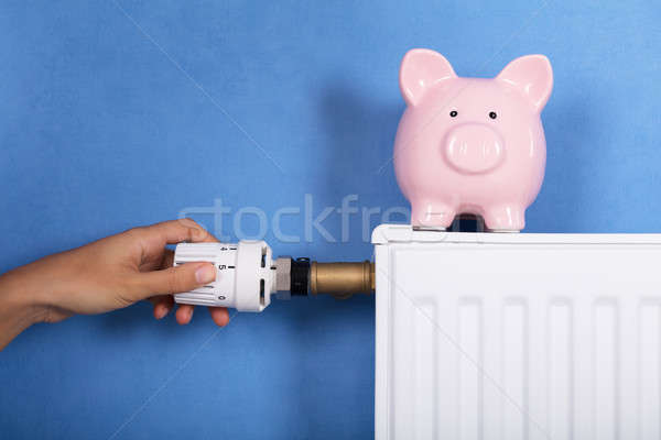 Stock photo: Person Hand Adjusting Temperature On Thermostat