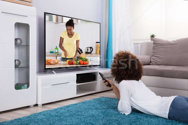 Nő tv nézés szőnyeg otthon étel televízió Stock fotó © AndreyPopov