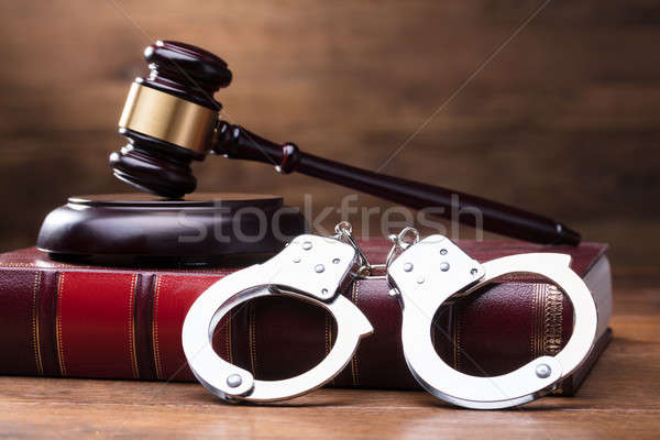 Gavel And Handcuffs On Law Book Stock photo © AndreyPopov