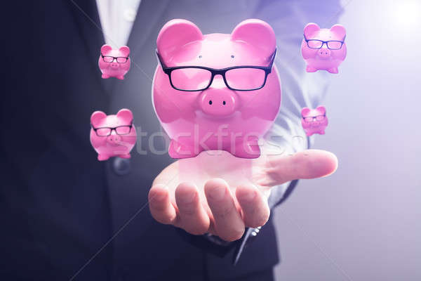 Piggy Banks Floating In Mid-air Over Businessperson's Hand Stock photo © AndreyPopov
