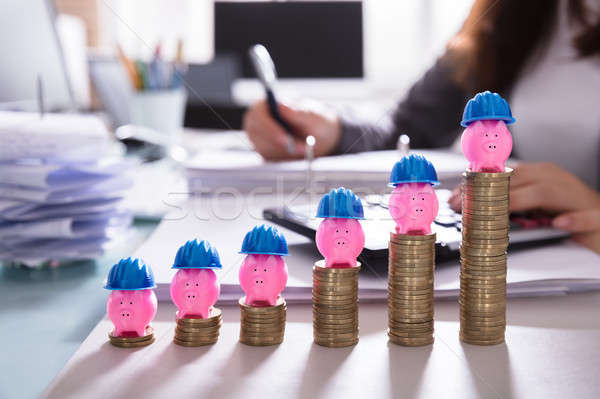 Pink Piggybank With Hard Hat Over Increasing Stacked Coins Stock photo © AndreyPopov