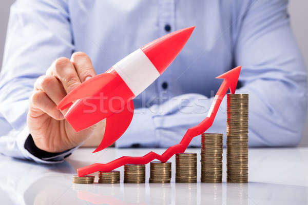 Businessperson Flying Rocket Over Increasing Graph Of Coins Stock photo © AndreyPopov