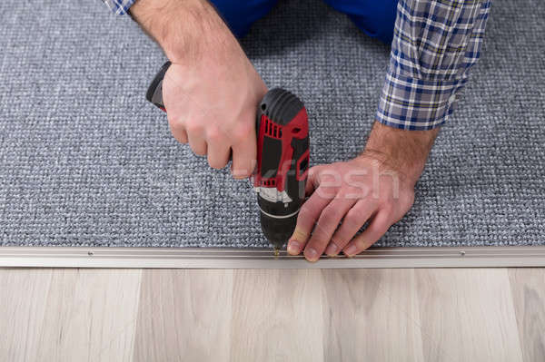 Carpet Fitter Installing Carpet With Wireless Screwdriver Stock photo © AndreyPopov