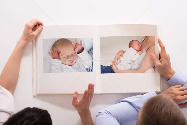 Couple Looking At Baby's Photo Album Stock photo © AndreyPopov