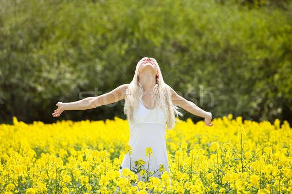 Foto stock: Mulher · jovem · em · pé · campo · sorridente · flores