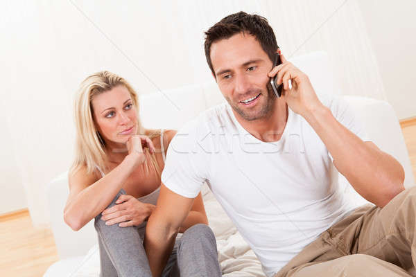 Man talking on his mobile watched by his wife Stock photo © AndreyPopov