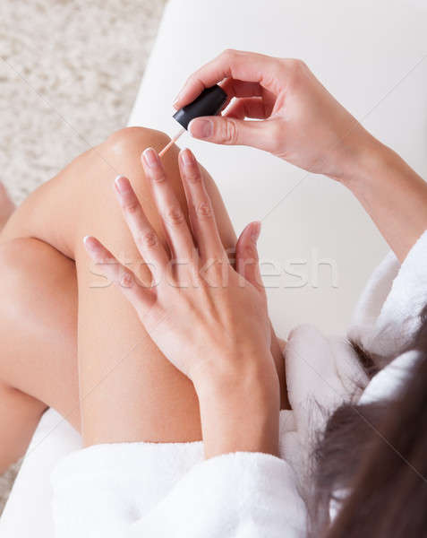 Woman sitting painting her nails Stock photo © AndreyPopov