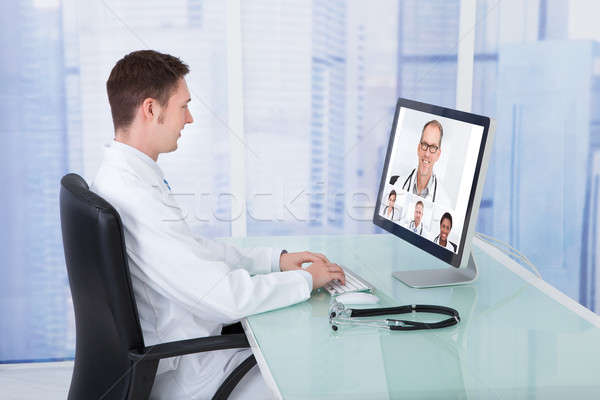 Doctor Video Conferencing With Colleagues Through Computer Stock photo © AndreyPopov