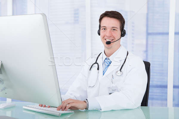 Doctor Wearing Headset While Using Computer At Desk Stock photo © AndreyPopov