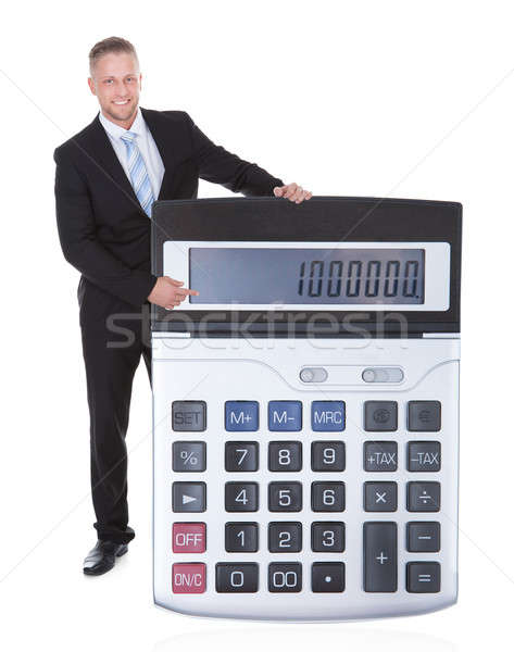 Smiling businessman displaying a calculator Stock photo © AndreyPopov