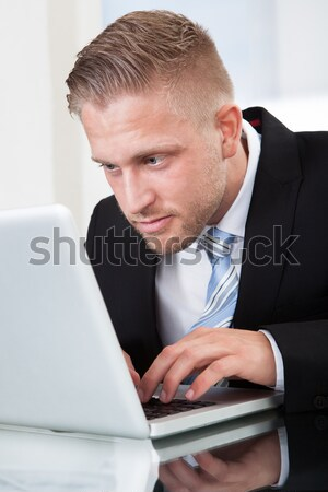 Businessman leaning forward at his laptop screen Stock photo © AndreyPopov
