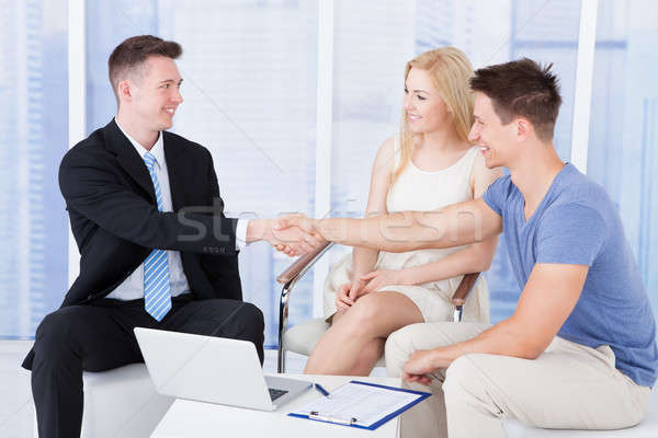 Young Couple Shaking Hands With Financial Consultant Stock photo © AndreyPopov