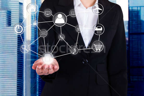 Businesswoman Holding Linked Virtual Icons Stock photo © AndreyPopov