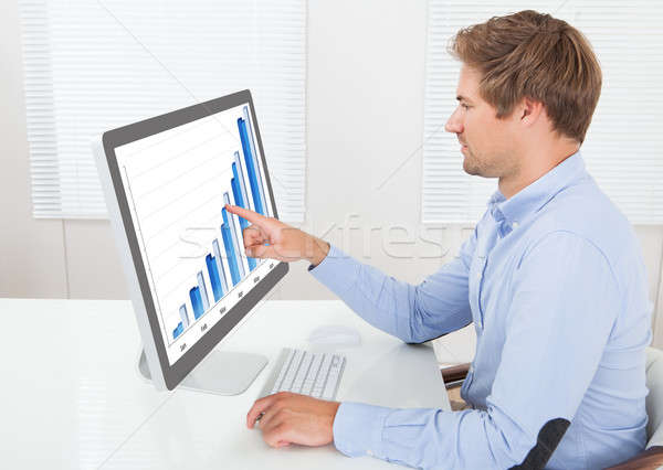 Businessman Analyzing Financial Graphs In Office Stock photo © AndreyPopov