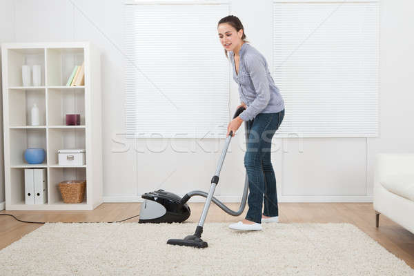 Woman Vacuuming Rug At Home Stock photo © AndreyPopov
