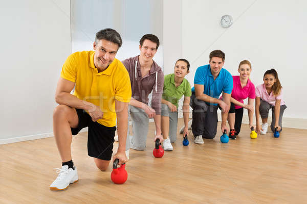 Mature Fitness Instructor With People Exercising Stock photo © AndreyPopov