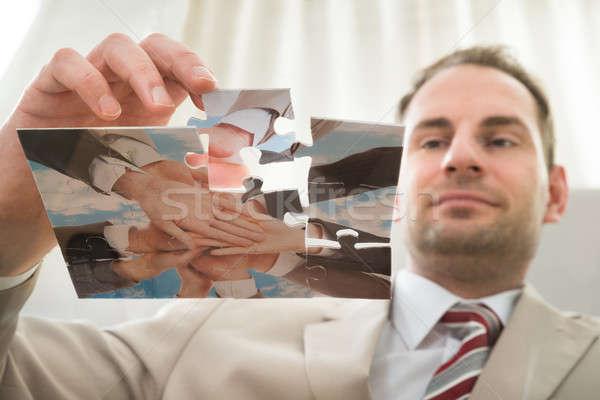 Businessman Inserting Last Puzzle Piece Stock photo © AndreyPopov