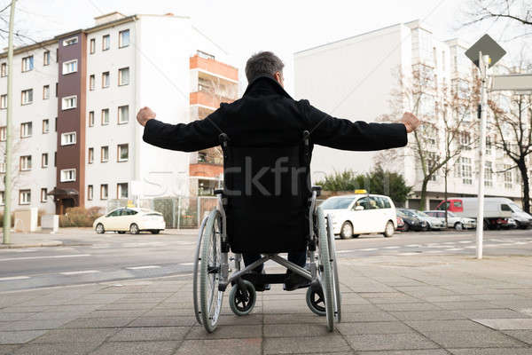Disabled Man On Wheelchair With Hand Raised Stock photo © AndreyPopov