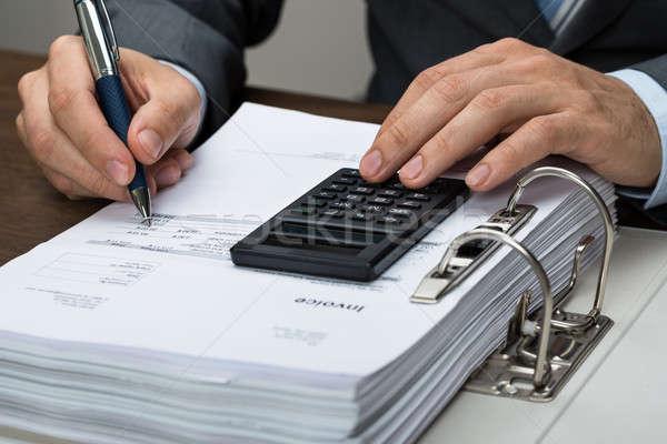 Businessman Calculating Bills In Office Stock photo © AndreyPopov