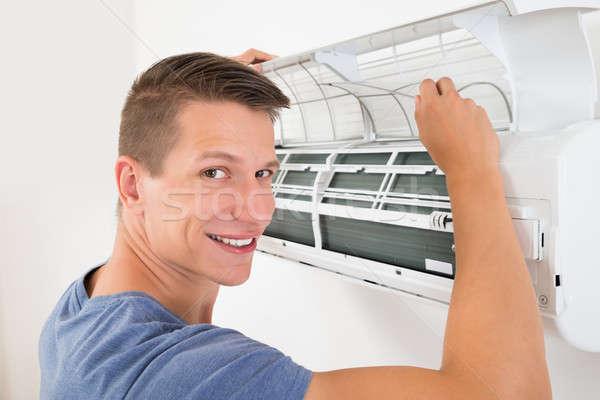 Hombre limpieza aire acondicionado jóvenes feliz trabajo Foto stock © AndreyPopov