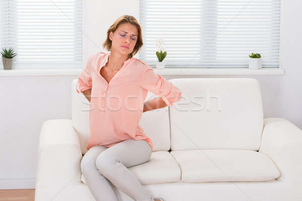 Woman On Sofa Suffering From Backache Stock photo © AndreyPopov