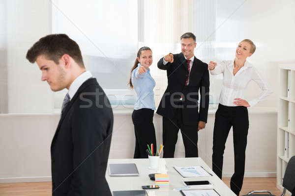 Businesspeople Teasing Businessman In Office Stock photo © AndreyPopov