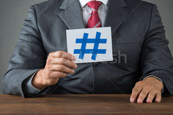 Businessman Showing Hash Sign At Desk Stock photo © AndreyPopov