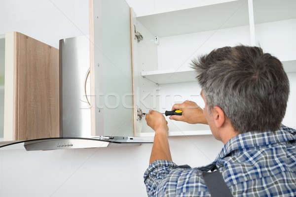 Serviceman Fixing Cabinet With Screwdriver In Kitchen Stock photo © AndreyPopov