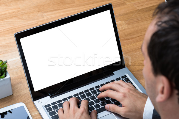 Businessman Using Laptop With Blank Screen At Desk Stock photo © AndreyPopov