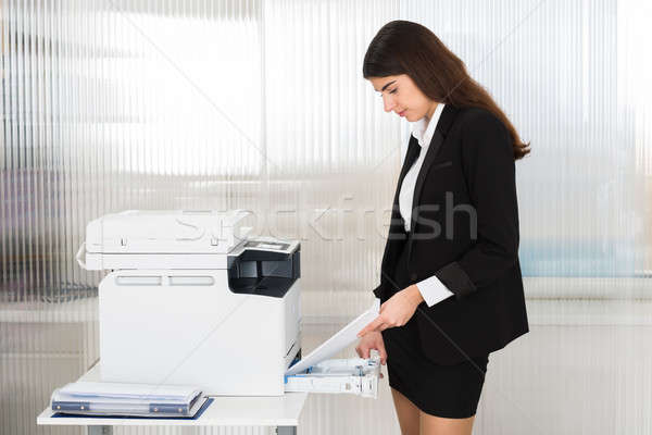 Young Businesswoman Inserting Papers In Photocopy Machine Stock photo © AndreyPopov