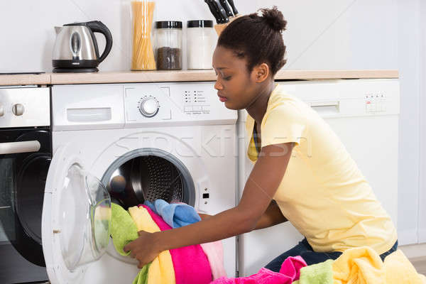 Woman Putting Clothes Into Washing Machine Stock photo © AndreyPopov