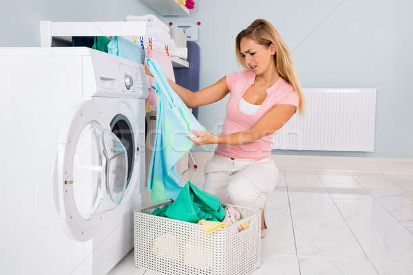 Woman Looking At Blue T-shirt After Laundering Stock photo © AndreyPopov