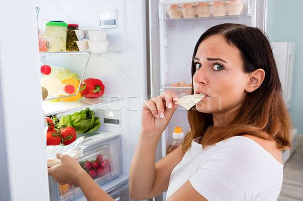 Vrouw eten kaas koelkast jonge vrouw plakje Stockfoto © AndreyPopov