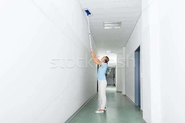 Donna pulizia soffitto corridoio costruzione Foto d'archivio © AndreyPopov