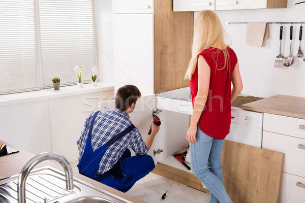 Male Worker Repairing Drawer In Kitchen Stock photo © AndreyPopov