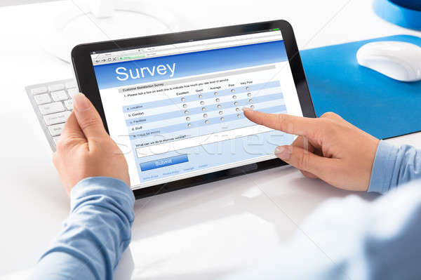 Woman Holding Digital Tablet With An Online Survey Form Stock photo © AndreyPopov