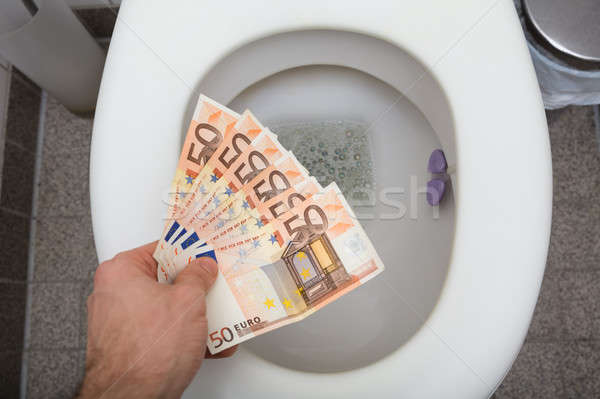 Man's Hand Throwing Fifty Euro Notes In Toilet Stock photo © AndreyPopov