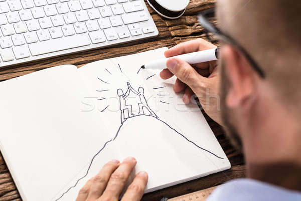 Businessman Drawing The Figures Giving High Five On Notebook Stock photo © AndreyPopov