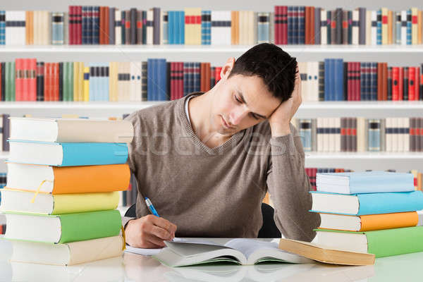Stressful University Student Studying In Library Stock photo © AndreyPopov