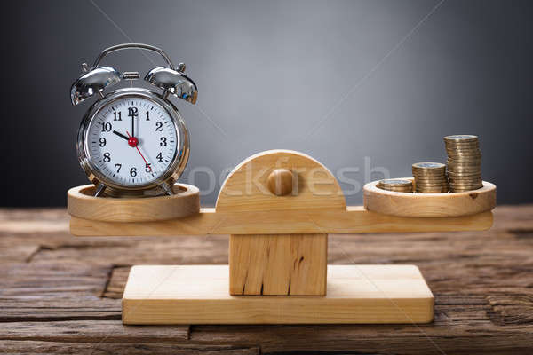 Clock And Coins Balancing On Wooden Weighing Scale Stock photo © AndreyPopov