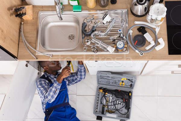 Handyman Lying On Floor Repairing Sink Stock photo © AndreyPopov