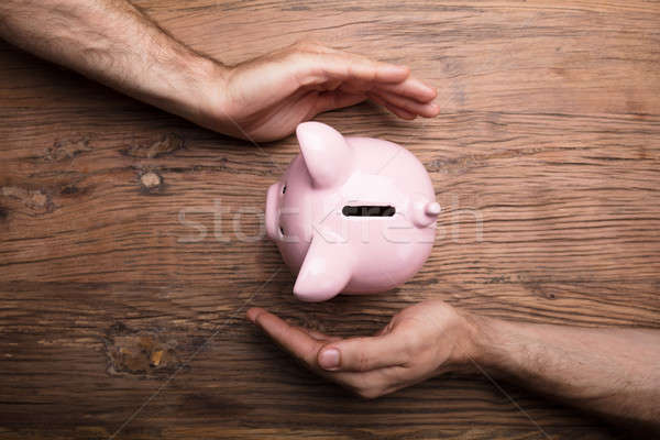 Hands Protecting Piggy Bank On Wooden Table Stock photo © AndreyPopov