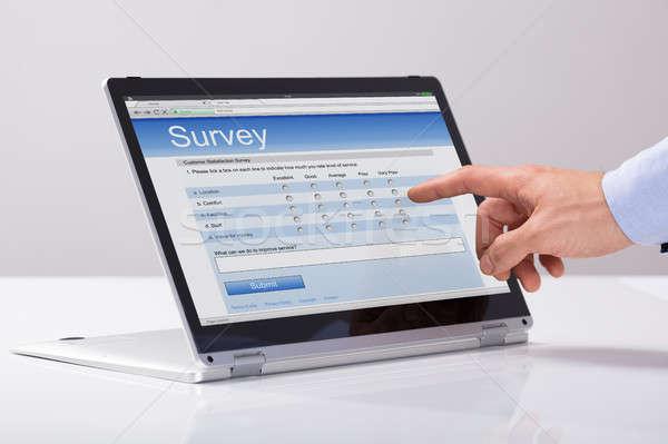 Businessman Filling Online Survey Form On Hybrid Laptop Stock photo © AndreyPopov