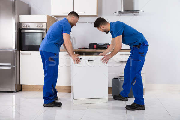 Two Movers Placing Dishwasher In Kitchen Stock photo © AndreyPopov