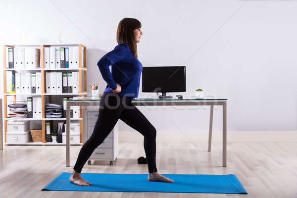 Businesswoman Doing Workout In Office Stock photo © AndreyPopov