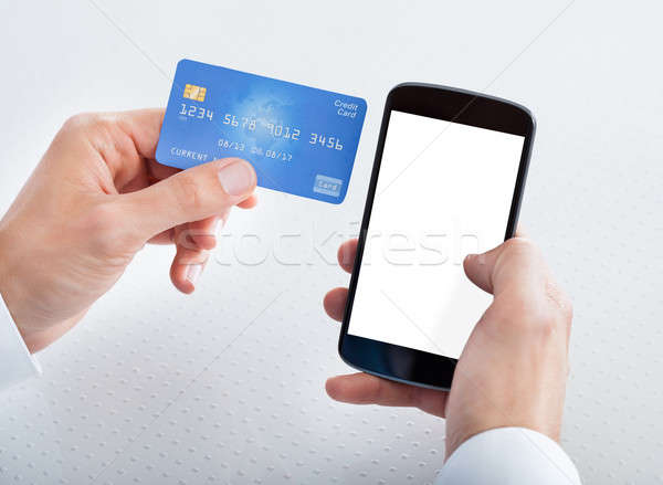 Man Holding Credit Card And Cell Phone Stock photo © AndreyPopov